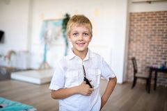 Boy holding big hair clippers. Young handsome boy, blond white hair, style official short-sleeved shirt, holding big hair clippers. Role-playing hairdresser or royalty free stock photos