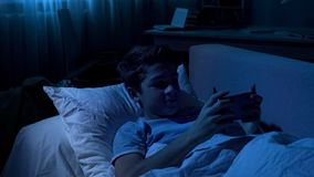 Young handsome boy playing on smartphone at night, gadget addiction, discipline. Stock photo royalty free stock image