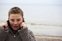 Young handsome boy with pullover at beach in winte Royalty Free Stock Image