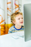Young handsome boy is watching on a computer screen Stock Photos