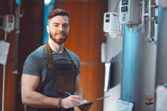 A young handsome brewer in an apron with a tablet in his hands a royalty free stock image