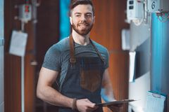 A young handsome brewer in an apron with a tablet in his hands a royalty free stock photo