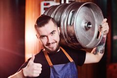 Handsome brewer man with a barrel of beer royalty free stock photography