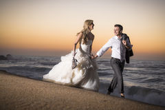 Young handsome bridal couple along beach at sunrise. Holding shoes and jacket Stock Image