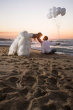 Young handsome bridal couple relaxing along beach at sunrise Royalty Free Stock Image
