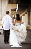 Young handsome bridal couple walking outdoors in urban area Royalty Free Stock Images