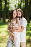 Young handsome brunette man gently hugs his beautiful wife and little daughter in the park on a sunny day stock photo