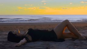 Sensual young brunette woman lies and relaxes on sandy beach at sunset stock video