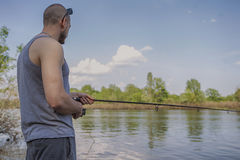 Young handsome brutal caucasian man in casual outfit fishing on Stock Photography