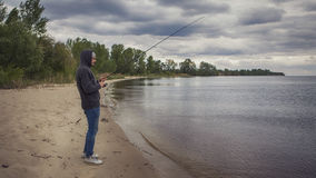 Young handsome brutal caucasian man in casual outfit fishing on Royalty Free Stock Photos