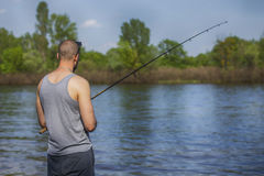 Young handsome brutal caucasian man in casual outfit fishing on Stock Photo