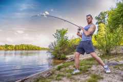Young handsome brutal caucasian man in casual outfit fishing on Stock Photos