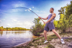 Young handsome brutal caucasian man in casual outfit fishing on. A lake as a hobby, trying to catch carp on spinning rod alone. Summer weather, sunset, natural Royalty Free Stock Images