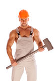 Young and handsome builder with a sledgehammer and Stock Photo