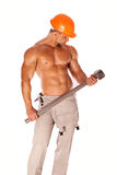Young and handsome builder with a sledgehammer and Stock Photography