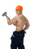 Young and handsome builder with a sledgehammer and sexy body Stock Photography
