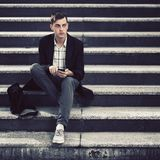Young handsome business man using smart phone on the steps Royalty Free Stock Photos