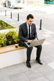Young Business Man Drinks Coffee While Using Laptop Outdoor. Young Handsome Business Man Drinks Coffee While Using Laptop Outdoor Stock Images