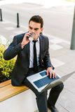 Young Business Man Drinks Coffee While Using Laptop Outdoor. Young Handsome Business Man Drinks Coffee While Using Laptop Outdoor Royalty Free Stock Photography