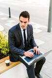 Young Business Man Drinks Coffee While Using Laptop Outdoor. Young Handsome Business Man Drinks Coffee While Using Laptop Outdoor Royalty Free Stock Image