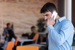 A young, handsome business man at the office building on phone Royalty Free Stock Image