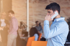 A young, handsome business man at the office building on phone Stock Images