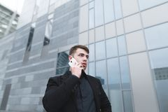 Portrait of a serious young businessman with a beard who speaks by phone on the background of modern ariculture. Stock Photo