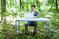 Young handsome business man sitting at office desk in the green park or forest and work at laptop while talk at phone with costume Stock Photography