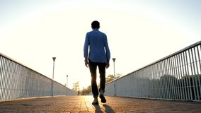 Young handsome business man or student walking alone on empty bridge or street. Back view. Traveling the world. Success
