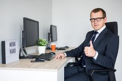 Young handsome business man thumbs up in modern office. Portrait of young handsome business man thumbs up in modern office stock image