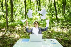 Young handsome business man at work table office with laptop in green forest with fly papers blank over head celebrate victory. Bu Stock Photo