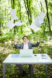 Young handsome business man at work table office with laptop in green forest with fly papers blank over head happy of end of proje Stock Image
