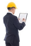 Young handsome business man in yellow builder's helmet writing s Royalty Free Stock Photography