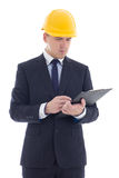 Young handsome business man in yellow builder's helmet writing s Royalty Free Stock Photos