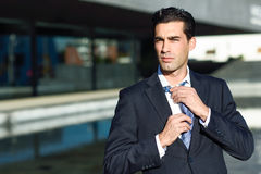 Young handsome businessman adjusting a tie in urban background Royalty Free Stock Photos