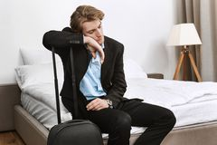 Young handsome businessman in black suit fall asleep with suitcase in hotel room after long trip in plane on business. Mission Royalty Free Stock Images