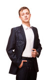 Young handsome businessman in black suit is standing straight and putting his hands in pockets, portrait isolated on Stock Photo
