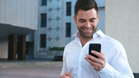 Young Handsome Businessman Celebrating Success while Reading Message in Smartphone near office building. Business stock video footage