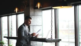 A young handsome businessman checks documents and typing on a laptop sitting in a cafe by the window stock footage