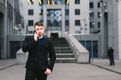 Young handsome businessman in a dark suit and talking on the phone on the background of modern architecture Stock Images