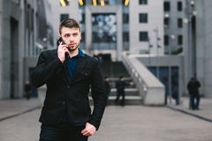 Young handsome businessman in a dark suit and talking on the phone on the background of modern urban landscape. Royalty Free Stock Images