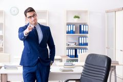 The young handsome businessman employee working in office at desk. Young handsome businessman employee working in office at desk Royalty Free Stock Image