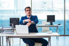 The young handsome businessman employee working in office at desk. Young handsome businessman employee working in office at desk Stock Image