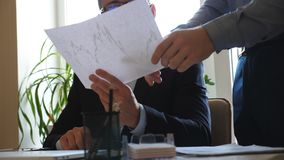 Young handsome businessman in eyeglasses holding paper with statistical graph in hands and giving instruction for male. Worker in office. Concept of business stock video footage