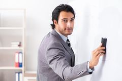 The young handsome businessman in front of whiteboard stock photo