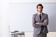 The young handsome businessman in front of whiteboard. Young handsome businessman in front of whiteboard stock images