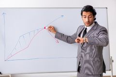 The young handsome businessman in front of whiteboard. Young handsome businessman in front of whiteboard royalty free stock photography