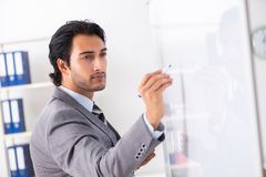 Young handsome businessman in front of whiteboard royalty free stock photography