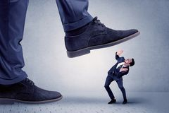 Young businessman getting crushed. Young handsome businessman getting crushed by a big formal shoe stock image