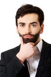 Young handsome businessman with hand under chin. Royalty Free Stock Photography